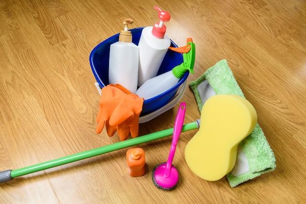 Volledige doos met schoonmaakproducten, mop en handschoenen op houten achtergrond