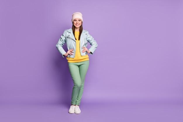 Volledige foto van aantrekkelijke dame lente weer mooie dag straat kleding glimlachend goed humeur draag casual hoed blauwe moderne jas groene broek schoenen geïsoleerde paarse kleur achtergrond