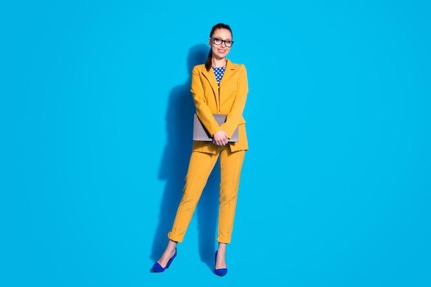 Volledige foto van aantrekkelijke zakelijke dame werknemer houden laptop online vergadering dragen bril gele blazer pak gestippelde blouse shirt hoge hakken geïsoleerde heldere blauwe kleur achtergrond