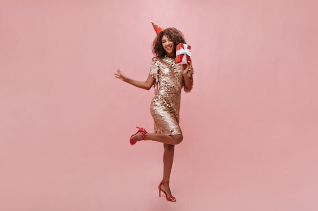 Volledige foto van afrikaanse vrouw met golvend kapsel in glanzende beige jurk, rode hakken en vakantiepet poseren met geschenkdoos op roze muur..