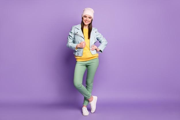 Volledige foto van coole aantrekkelijke dame lente weer mooie dag straat kleding glimlachend goed humeur draag casual hoed blauwe moderne stijl jas groene broek geïsoleerde paarse kleur achtergrond