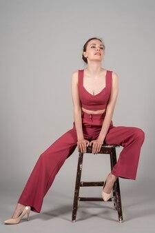 Volledige foto van een aantrekkelijke, chique zakelijke dame die een stoel draagt, een rood pak met hoge hakken draagt, een geïsoleerde grijze achtergrond