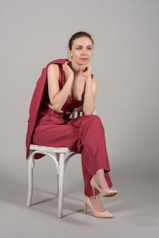 Volledige foto van een aantrekkelijke, chique zakelijke dame die een stoel draagt, een rood pak met hoge hakken, een geïsoleerde grijze achtergrond