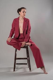 Volledige foto van een aantrekkelijke, chique zakenvrouw die op een stoel zit en een rood pak draagt, een geïsoleerde grijze achtergrond