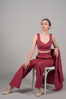 Volledige foto van een aantrekkelijke, chique zakenvrouw die op een stoel zit en rode hoge hakken draagt i