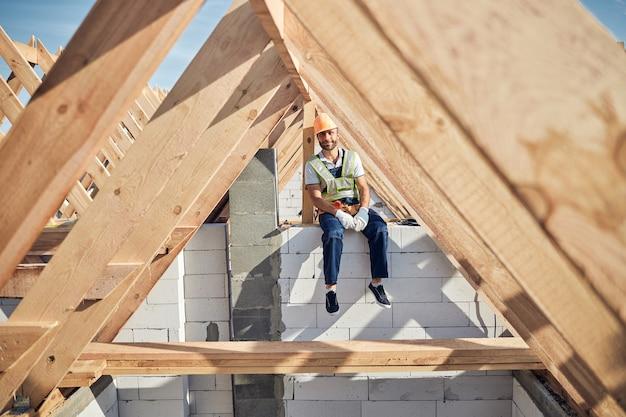 Volledige foto van een architect die een helm draagt terwijl hij op een muur van een gebouw zit en naar de camera kijkt