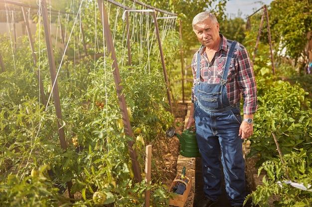 Volledige foto van een bejaarde die in zijn tuin staat met een gieter en naar de camera kijkt