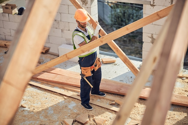 Volledige foto van een bouwer met volledige uitrusting in een veiligheidshelm die hout draagt voor de bouw