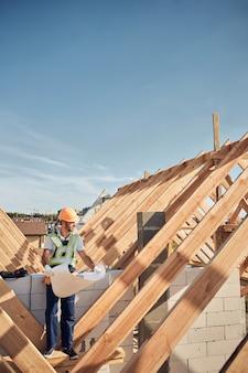 Volledige foto van een drukke bouwer die een enorme blauwdruk vasthoudt en naar de bouwplaats kijkt