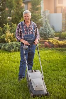 Volledige foto van een grijsharige man die een spijkerbroek draagt en zijn groene gazon maait