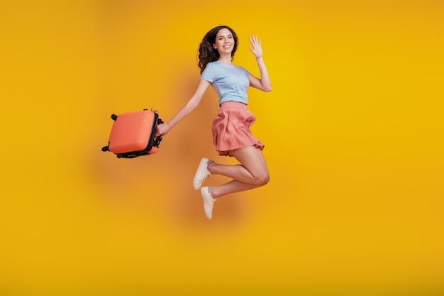 Volledige foto van een jonge, aantrekkelijke vrouw met een gelukkige positieve glimlach koffer reis golf hallo geïsoleerd over gele kleur achtergrond