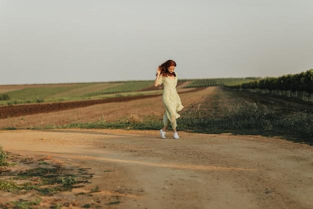 Volledige foto van een jonge vrouw met gemberachtig golvend haar in een lange, stijlvolle groene en gele jurk en lichte sneakers die aan de muur van het veld poseren