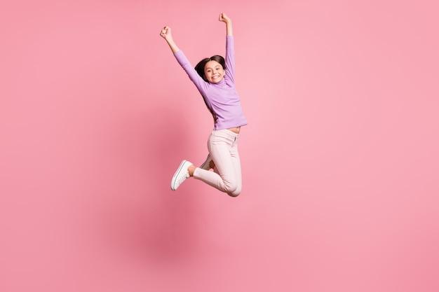 Volledige foto van een klein meisje dat springt, handen opsteekt en een paarse trui draagt, geïsoleerd op een pastelkleurige achtergrond