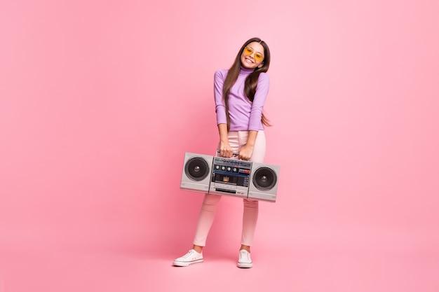 Volledige foto van een klein meisje met een cassette-retro-boomdoos met een paarse broek, geïsoleerd op een pastelkleurige achtergrond