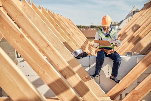 Volledige foto van een man met een helm die naar een klembord kijkt terwijl hij op de bouwplaats zit