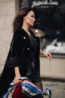 Volledige foto van een mooie elegante vrouw die op straat loopt terwijl ze een zijden sjaal op haar hoofd draagt. schoonheid en mode concept