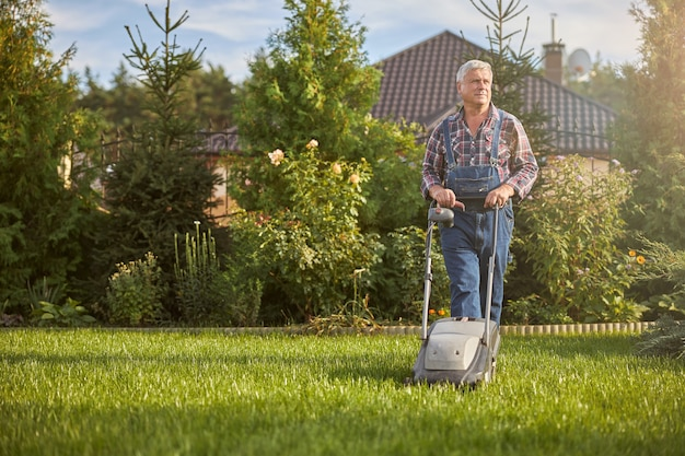 Volledige foto van een oudere man die een grasmaaier gebruikt om het gras op zijn gazon te trimmen