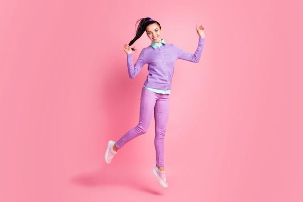 Volledige foto van een vrolijk meisje dat springt, haar staart vasthoudt en paarse kleding draagt, geïsoleerd op een pastelroze achtergrond
