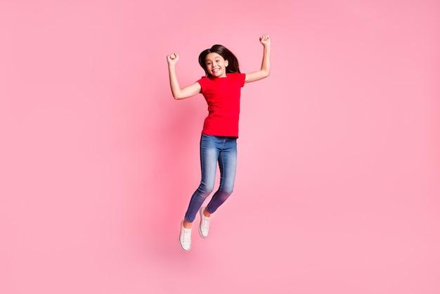 Volledige foto van een vrolijk meisje dat springt, vuisten opsteekt en een rood casual t-shirt draagt, geïsoleerd op een pastelkleurige achtergrond
