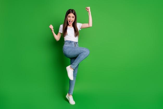 Volledige foto van een vrolijk winnaarmeisje, gekleed in een casual outfit, armen omhoog met open mond, geïsoleerde groene kleurachtergrond