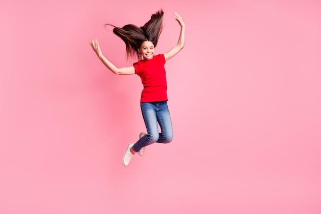 Volledige foto van een vrolijke jongen die springt met een vliegend lang kapsel en een casual outfit draagt, geïsoleerd op een pastelkleurige achtergrond