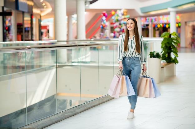 Volledige foto van een vrolijke, mooie meid, dame geniet van vrije tijd, koop, houd veel tassen, wandelen, winkelcentrumvloer, opgewonden om de volgende winkel te bezoeken, draag casual jeans, overhemd, schoenen, outfit binnenshuis