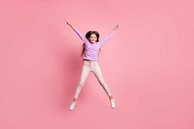 Volledige foto van een zorgeloos kindmeisje dat opspringt en handen opsteekt geïsoleerd over pastelkleurige achtergrond