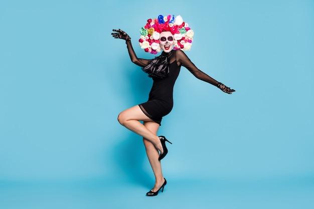Volledige foto van enge charmante zombie dame dans rollenspel oktober evenement draag zwarte kant korte mini jurk hoge hakken handschoenen dood kostuum rozen hoofdband geïsoleerde blauwe kleur achtergrond