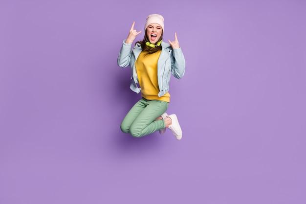 Volledige foto van funky aantrekkelijke dame stijlvolle kleding spring hoog verheugend rockconcert tonen vinger hoorns dragen casual hoed jas groene broek schoenen geïsoleerde paarse kleur achtergrond