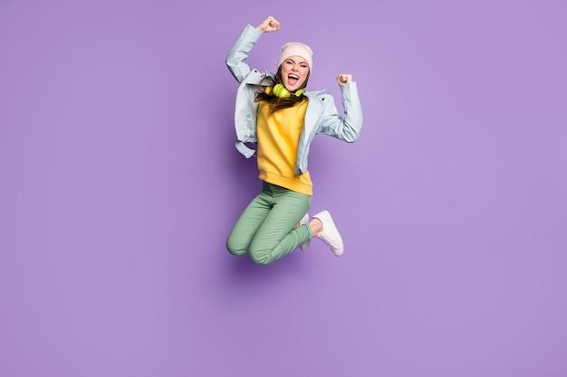 Volledige foto van funky aantrekkelijke dame stijlvolle kleding springen hoog vreugde kampioen persoon schreeuwen goed humeur dragen casual hoed jas groene broek schoenen geïsoleerde paarse kleur achtergrond