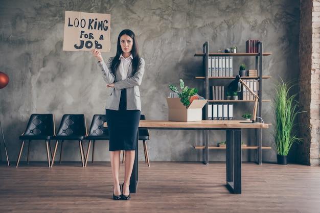 Volledige foto van gefrustreerd meisje ceo marketeer meisje verliest zoeken naar werk zoeken naar werk in coronavirus quarantaine crisis houd kartonnen tekst draag blazerpak stiletto's op werkplek werkstation