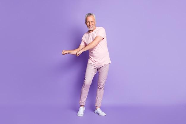 Volledige foto van gepensioneerde opa dansende vuisten dragen roze t-shirt broek sneakers geïsoleerde violette kleur achtergrond