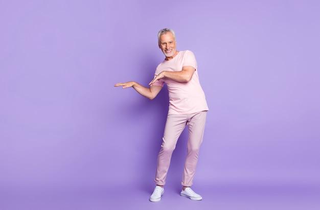 Volledige foto van gepensioneerde oude man dansarmen dragen roze t-shirt broek sneakers geïsoleerde paarse kleur achtergrond