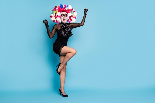 Volledige foto van griezelige gekke boze geest dame hef vuist op en word festival koningin draag zwarte kant korte mini jurk hoge hakken handschoenen dood kostuum rozen hoofdband geïsoleerde blauwe kleur achtergrond