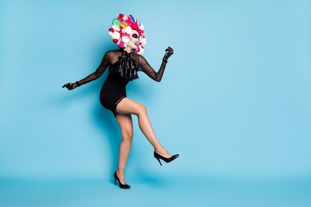 Volledige foto van griezelige monster dame dans zorgeloos festival samba slijtage zwarte kant korte mini jurk hoge hakken handschoenen dood kostuum rozen hoofdband geïsoleerde blauwe kleur achtergrond