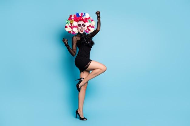 Volledige foto van griezelige schattige zombie dame raise vuist win cosplay concurrentie slijtage zwarte kanten korte mini jurk hoge hakken handschoenen dood kostuum rozen hoofdband geïsoleerde blauwe kleur achtergrond