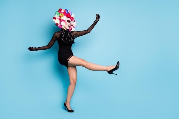 Volledige foto van griezelige vampier dame dans onvoorzichtig carnaval verhogen lange been dragen zwarte kant korte mini jurk hoge hakken handschoenen dood kostuum rozen hoofdband geïsoleerde blauwe kleur achtergrond