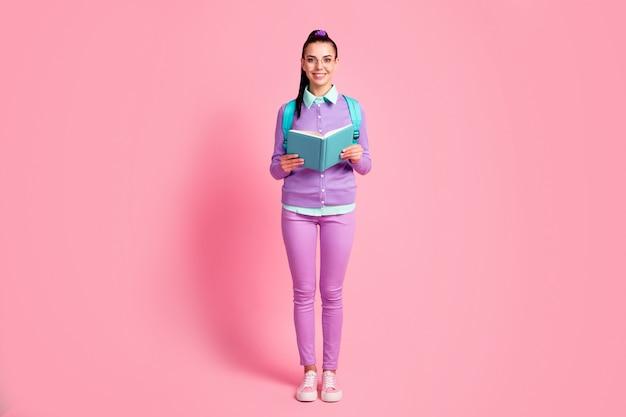 Volledige foto van jonge dame houdt boek kijk camera draagt specificaties tas violet pullover broek sneakers geïsoleerde roze kleur achtergrond