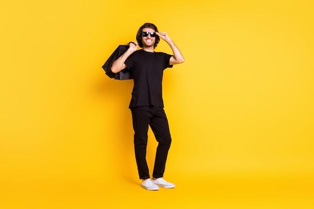 Volledige foto van jonge man die winkelpakketten vasthoudt, bril draagt zwarte t-shirt broek witte sneakers zonnebril geïsoleerde gele kleur achtergrond