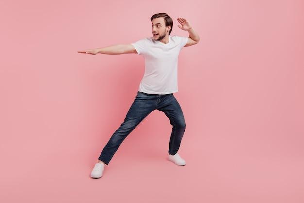 Volledige foto van knappe aantrekkelijke kerel karate training sportieve geïsoleerde roze kleur achtergrond