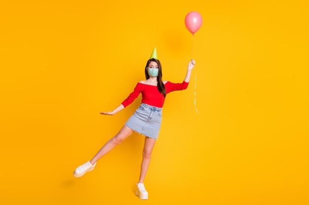 Volledige foto van mooi meisje in medisch masker vang lucht vlieg wind ballon draag rode top casual denim jeans rok benen geïsoleerd over heldere glans kleur achtergrond
