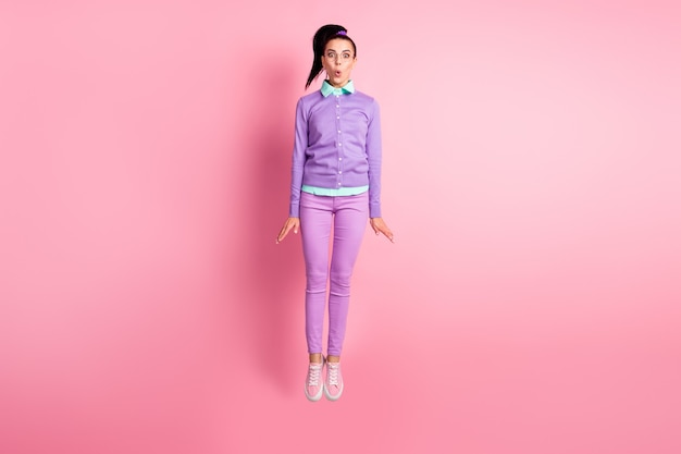 Volledige foto van mooie dame sprong verbaasd draag een bril violet jumper broek sneakers geïsoleerde roze kleur achtergrond