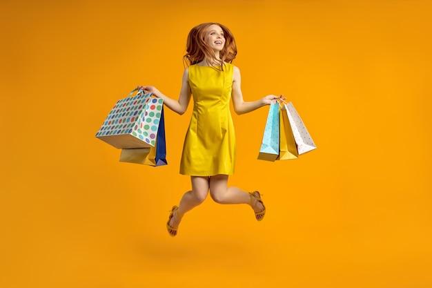 Volledige foto van mooie roodharige dame draagt veel winkelpakketten verslaafde shopaholic in gele jurk