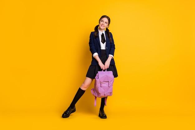 Volledige foto van nieuwsgierig, overweeg middelbare schoolmeisje, houd rugzak vast, kijk copyspace