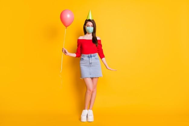 Volledige foto van positief meisje met medisch masker heeft feestelijke verjaardag covid quarantaine viering houd ballon draag rode top jeans rok benen kegel geïsoleerd heldere glans kleur achtergrond