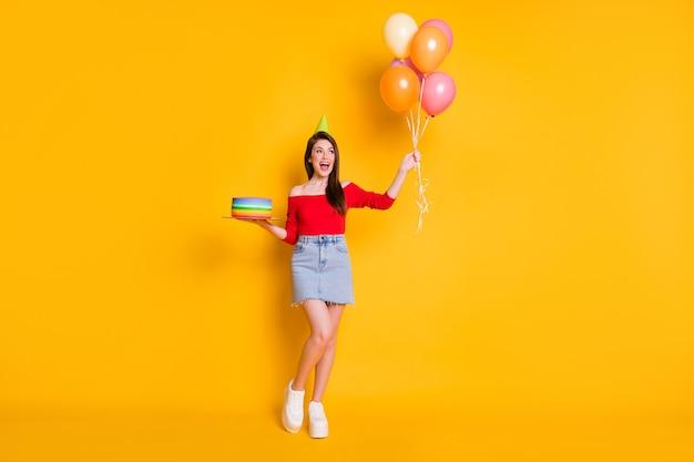 Volledige foto van positief vrolijk meisje geniet van verjaardagsfeestje, houd veel ballonnen, heldere verjaardagstaart, draag off-shoulder bovenbenen geïsoleerd over glanskleurachtergrond