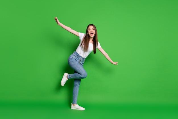 Volledige foto van schattige mooie dromerige dame steekt handen grappige vliegtuigdanskleding jeans t-shirt schoeisel geïsoleerde groene achtergrond op