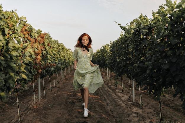 Volledige foto van stijlvol meisje met foxy kapsel en zwart verband op nek in groene jurk die loopt en lacht op wijngaarden