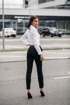 Volledige foto van stijlvolle vrouw gekleed in zwarte broek en wit overhemd en staande op straat tegen het moderne gebouw. stijl- en modeconcept