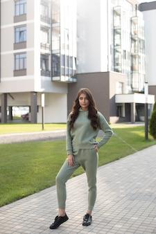 Volledige foto van stijlvolle vrouw in trendy sportkleding poseren op straat met gebouw op de achtergrond. vrouwelijke mode. stadslevensstijl